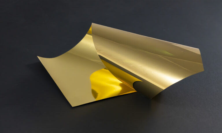 A thin roll of gold film curling upon itself on a black background